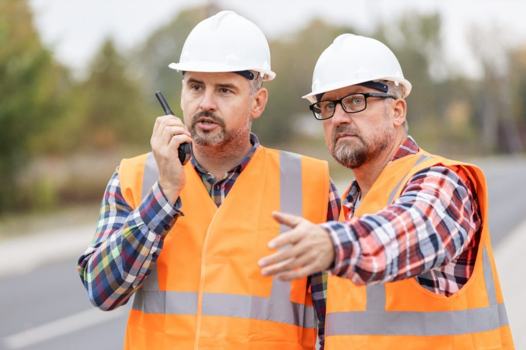 road construction workers talking to walkie talkie 9MPT6SM scaled e1587231493350